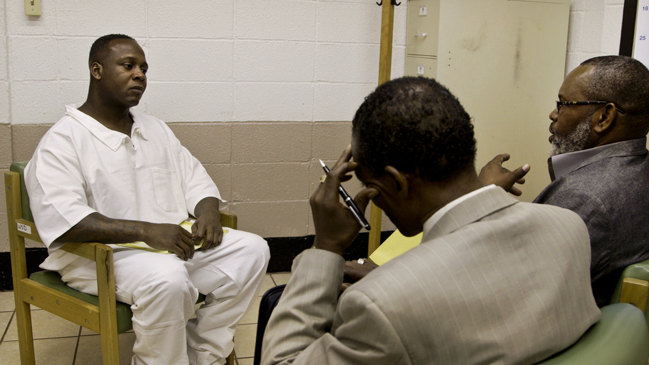 Billy Smith (right) and Johnny Lindsey (center) meet with prisoner Jimmy O'Steen. The group believes O'Steen is innocent and hopes its investigation can exonerate him.