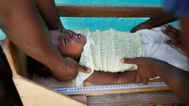 Renande Raphael, aged 16 months, is measured to check whether she is growing normally. She's part of a trial in Haiti to see if an extra daily snack of enriched peanut butter prevents stunting and malnutrition.