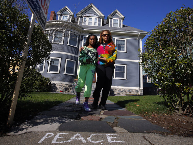 At the Richard family home in Dorchester, Mass., on Tuesday, Jacqueline Myers (right) and her 10-year-old daughter Amira were among those who came to grieve over the death of 8-year-old Martin Richard. He was killed by one of the blasts at Monday's Boston Marathon. His mother and sister were seriously injured.