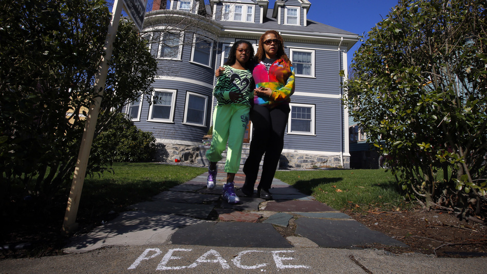 At the Richard family home in Dorchester, Mass., on Tuesday, Jacqueline Myers (right) and her 10-year-old daughter Amira were among those who came to grieve over the death of 8-year-old Martin Richard. He was killed by one of the blasts at Monday's Boston Marathon. His mother and sister were seriously injured. (Reuters /Landov)