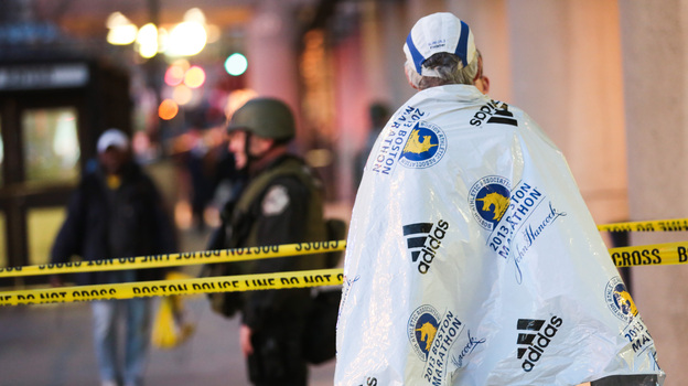 A marathon runner, wrapped in a blanket to stay warm after the race, watched Monday as authorities investigated the bombings that shook the finish line area at the Boston Marathon. At least three people were killed and dozens were wounded. (Barcroft Media /Landov)