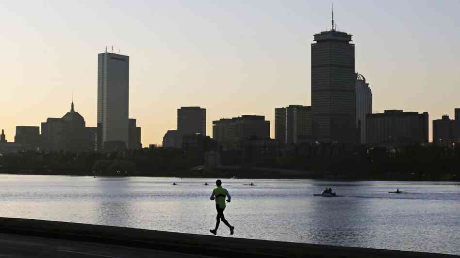A runner heads down the banks of the Charles River in Cambridge, Mass., in front of the Boston skyline at dawn, the morning after deadly explosions at the Boston Marathon.