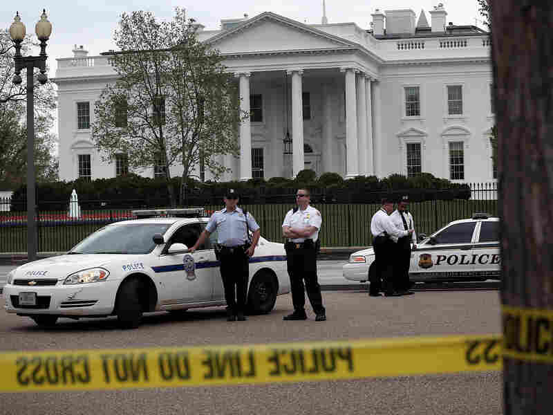 U.S. Secret Service and U.S. Park Police officers stand guard on Pennsylvania Avenue in front of the White House Monday. Security there was tightened after at least two explosions went off near the finish line of the Boston Marathon.