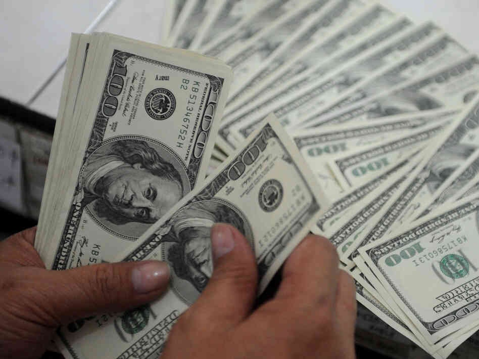 An employee at a money changer counts $100 bills in Manila on October 25, 2012.