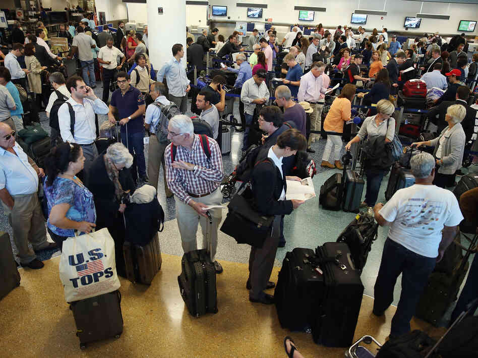 American Airlines passengers wait in line for a