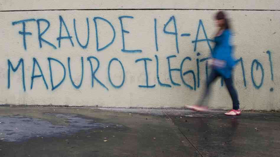 """A woman walks past a message painted on a wall in the streets of Caracas reading """"Fraud. Maduro Illegitimate."""""""