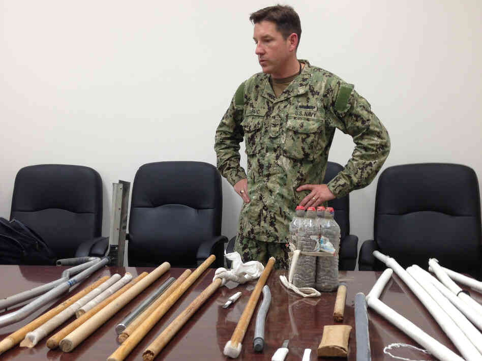 In this image reviewed by the U.S. military, Navy Capt. Robert Durand stands next to some of the makeshift weapons confiscated from detainees at the Guantanamo Bay prison following a clash Saturday between prisoners and guards.