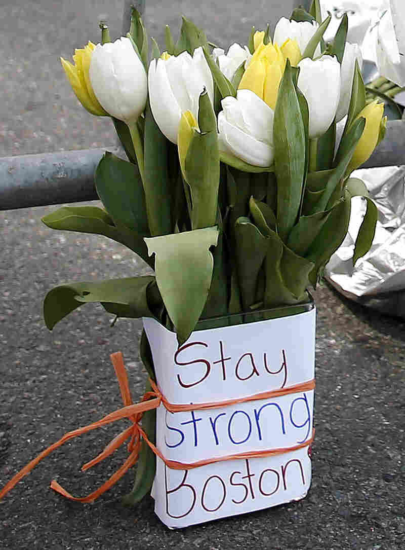 Flowers sit at a police barrier near the finish line of the Boston Marathon.