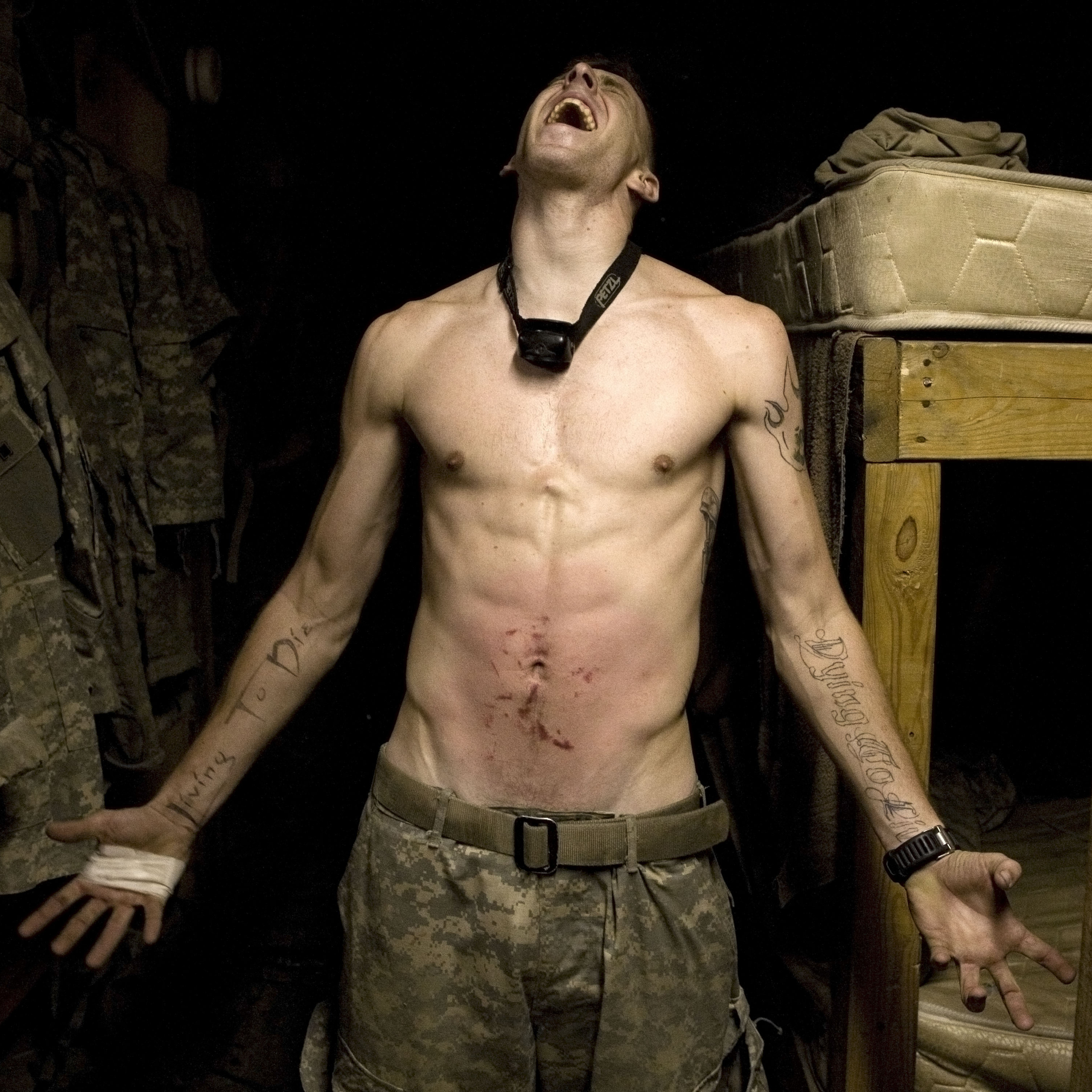 "Spc. Tad Donoho screams with pain in 2008 after being administered a ""pink belly"" for his birthday in Korengal Valley, Kunar province, Afghanistan. Each member of the platoon strikes his stomach until it begins to bruise, hence the name pink belly. From the book Infidel."