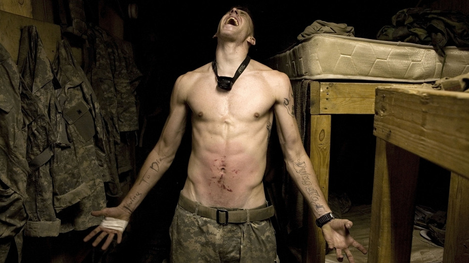 "Spc. Tad Donoho screams with pain in 2008 after being administered a ""pink belly"" for his birthday in Korengal Valley, Kunar province, Afghanistan. Each member of the platoon strikes his stomach until it begins to bruise, hence the name pink belly. From the book Infidel. (Magnum Photos)"