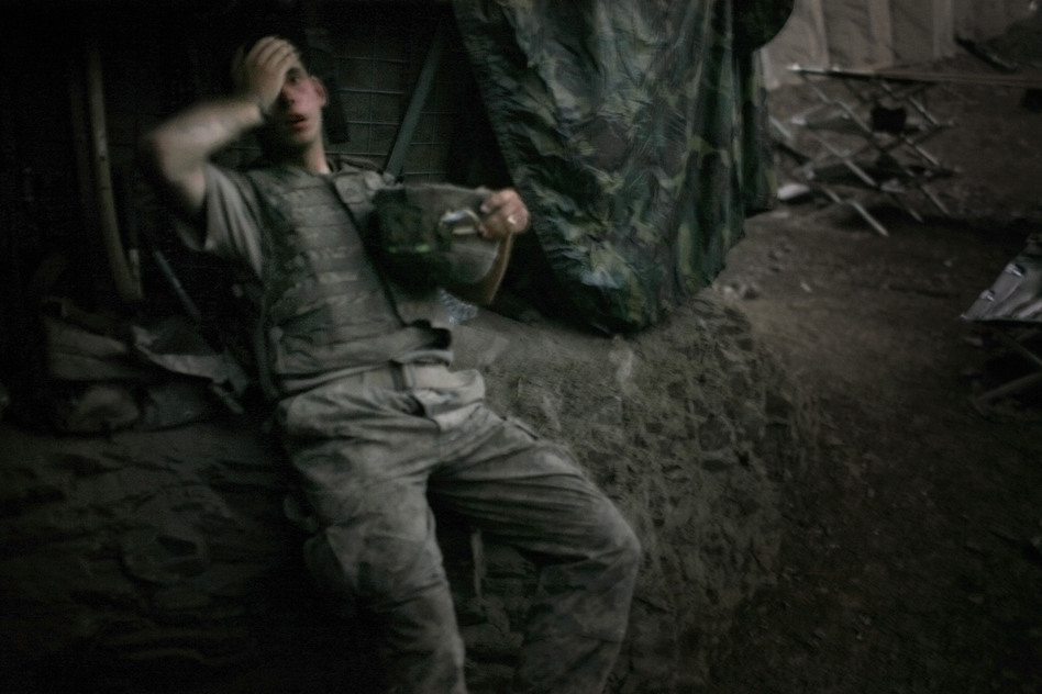 "A soldier rests at the end of a day of heavy fighting at the Restrepo outpost in Afghanistan's Korengal Valley. This image won the 2007 World Press Photo of the Year award. ""The funny thing about war, it actually almost never hardens people,"" Junger says. ""It almost always humanizes them, and I think war humanized Tim tremendously because it inflicted so much pain on him."" (Magnum Photos)"