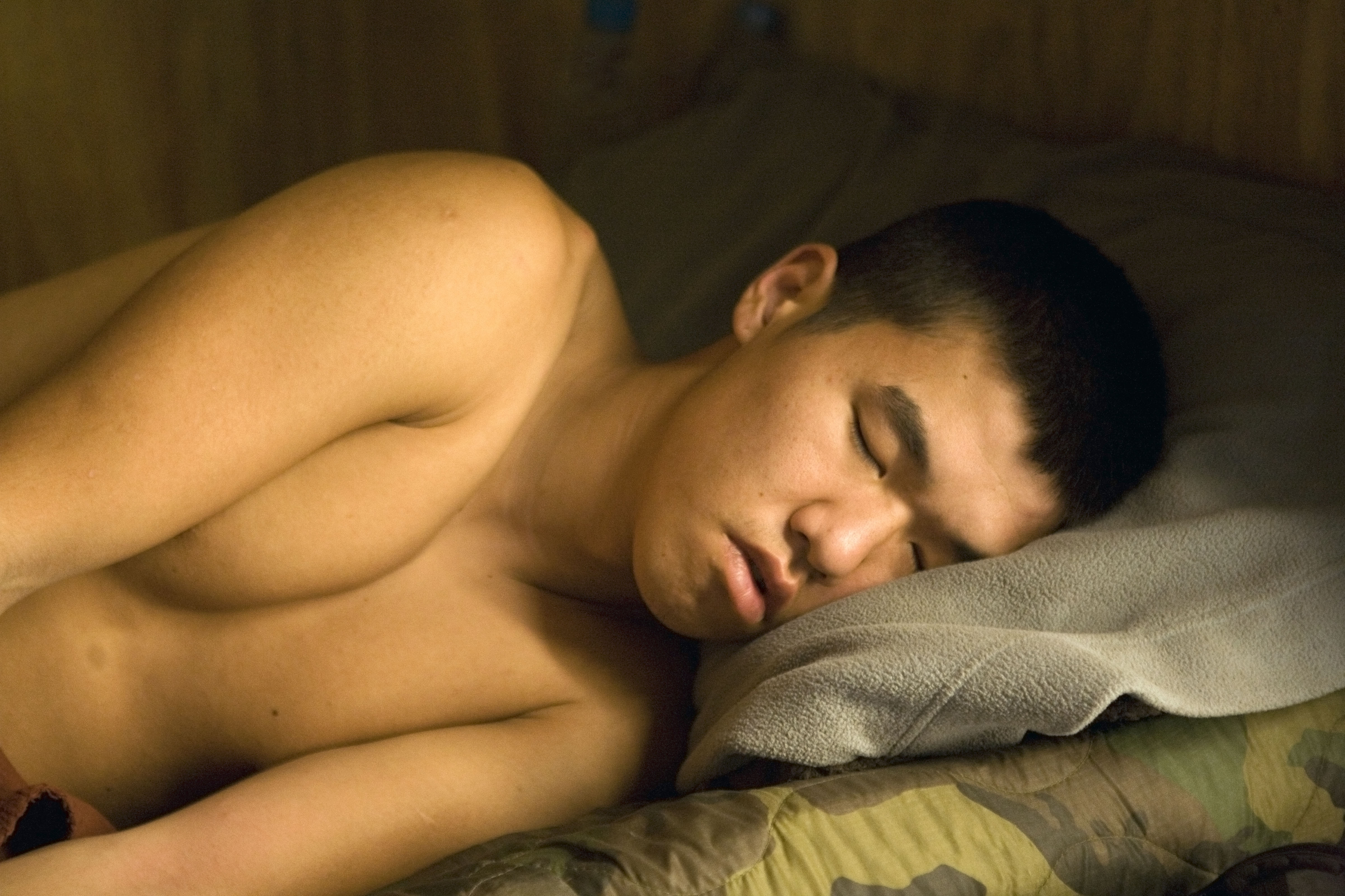 "Spc. Steve Kim sleeping, the Korengal, July 2008. "" 'We don't wanna know that they're also these vulnerable boys,' "" Hetherington told Junger."