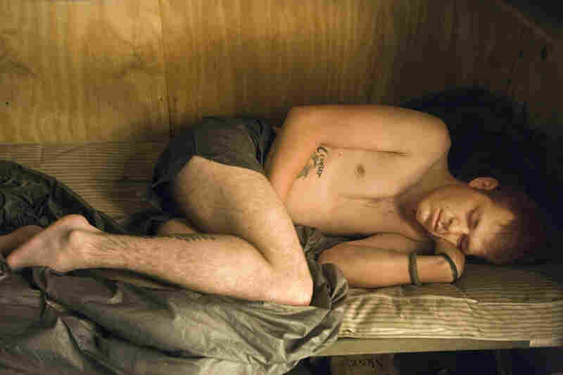 """""""Doc"""" Kelso sleeping, Korengal, July 2008. """"Soldiers in their combat fatigues, their gear, their weapons — they look very formidable,"""" Junger reflects. """"But then you take their gear off them and they go to sleep, and they really do look very vulnerable and very young."""""""