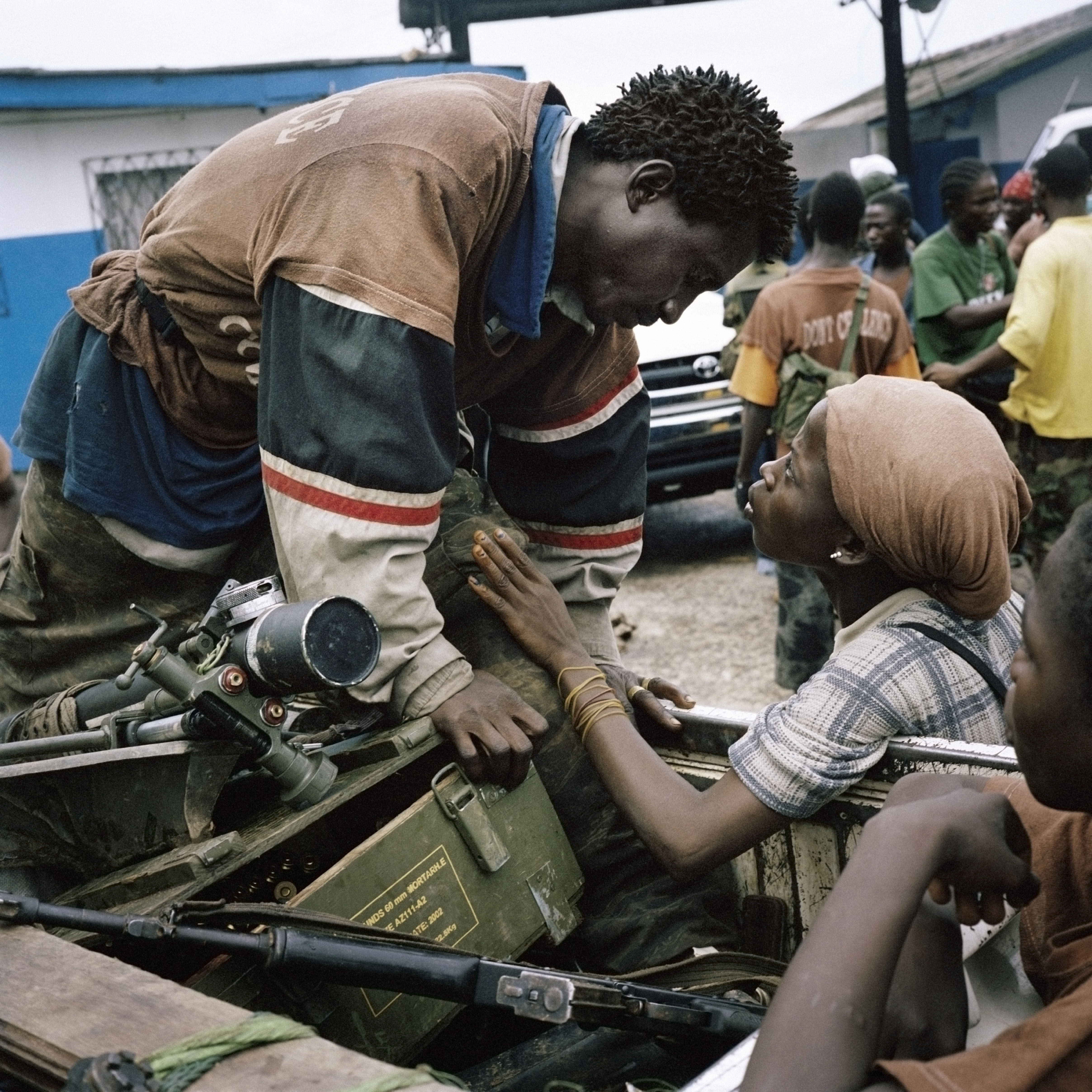 "An anti-aircraft brigade member exchanges a brief tender word with his girlfriend during heavy fighting in Monrovia in 2003. ""It's kind of an ugly environment ... and they're holding each other and they're looking at each other with just incredible love,"" Junger says. ""And it's just -- the look on both of their faces is so beautiful, and that's what Tim was looking for in war reporting."""