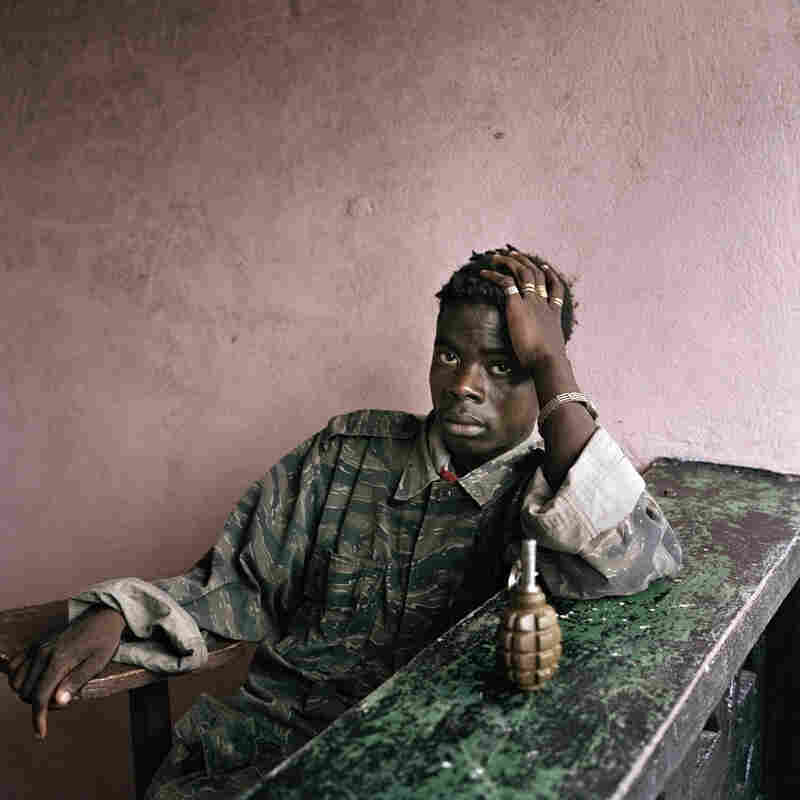 "A young rebel fighter with a hand grenade, Tubmanberg, Bomi County, Liberia, 2003. ""It wasn't the ugliness; it was the beauty and the love that happens in those very intense situations,"" Junger says. ""And [Tim] would capture it."""