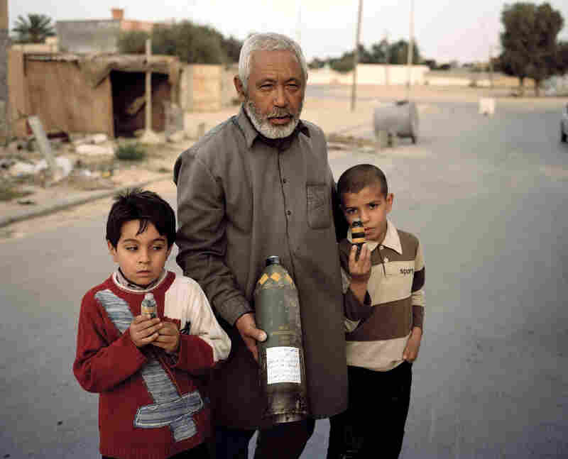 "Members of a Libyan family with undetonated ordnance, reportedly fired into their homes by Gadhafi forces, in Misrata, Libya. ""Where I got nervous was when he emailed me and said he was going to Misrata by boat,"" Junger remembers. ""Something about that just seemed rife with potential problems: a besieged city, you can only get in and out by boat. ... It just seemed like it could go really badly."""