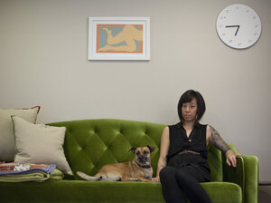Graphic designer Kaleena Porter sits with her dog, Moby, in the living room of her new home in Washington, D.C.