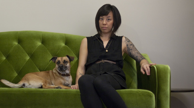Graphic designer Kaleena Porter sits with her dog, Moby, in the living room of her new home in Washington, D.C. (NPR)