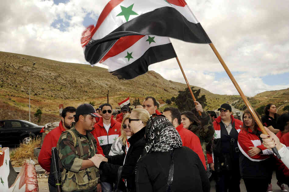 This photo, from the official Syrian Arab News Agency (SANA), shows members of the Damascus Youth volunteer group visiting Syrian soldiers at a checkpoint in Damascus, on the country's national day.
