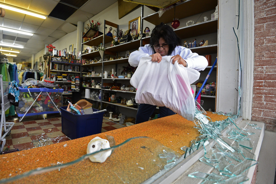 Maria Galvin cleans up broken glass in the front of her business, after the windows was blown out by the explosion. (EPA/Landov)