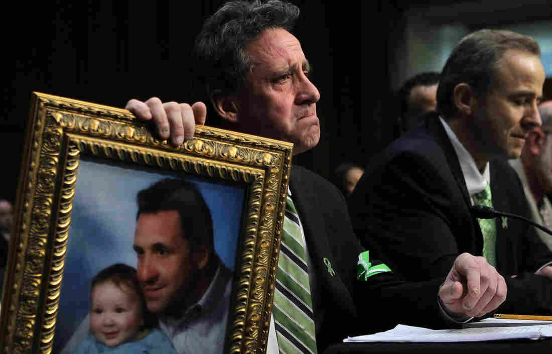 Neil Heslin, father of 6-year-old Sandy Hook Elementary School shooting victim Jesse Lewis, holds a picture of the two of them as he testifies during a hearing before the Senate Judiciary Committee in February.
