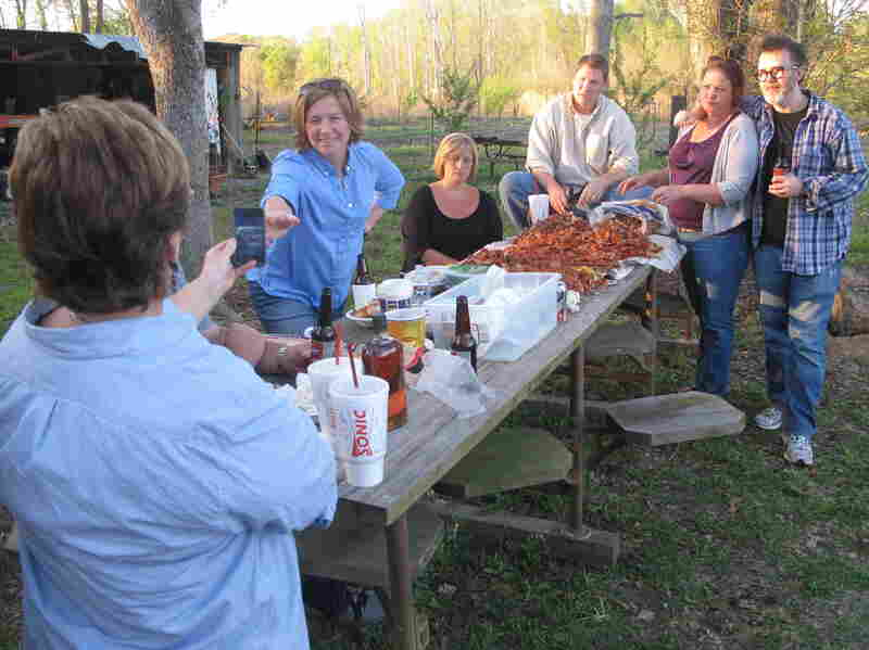"Ruthie Leming's friends and Rod Dreher (right) gather for a crawfish boil at Ronnie Morgan's camp by the Starhill Riviera. ""When I'm gone,"" Morgan says, ""the only thing that's going to show up to say I was here is the people I left behind."""