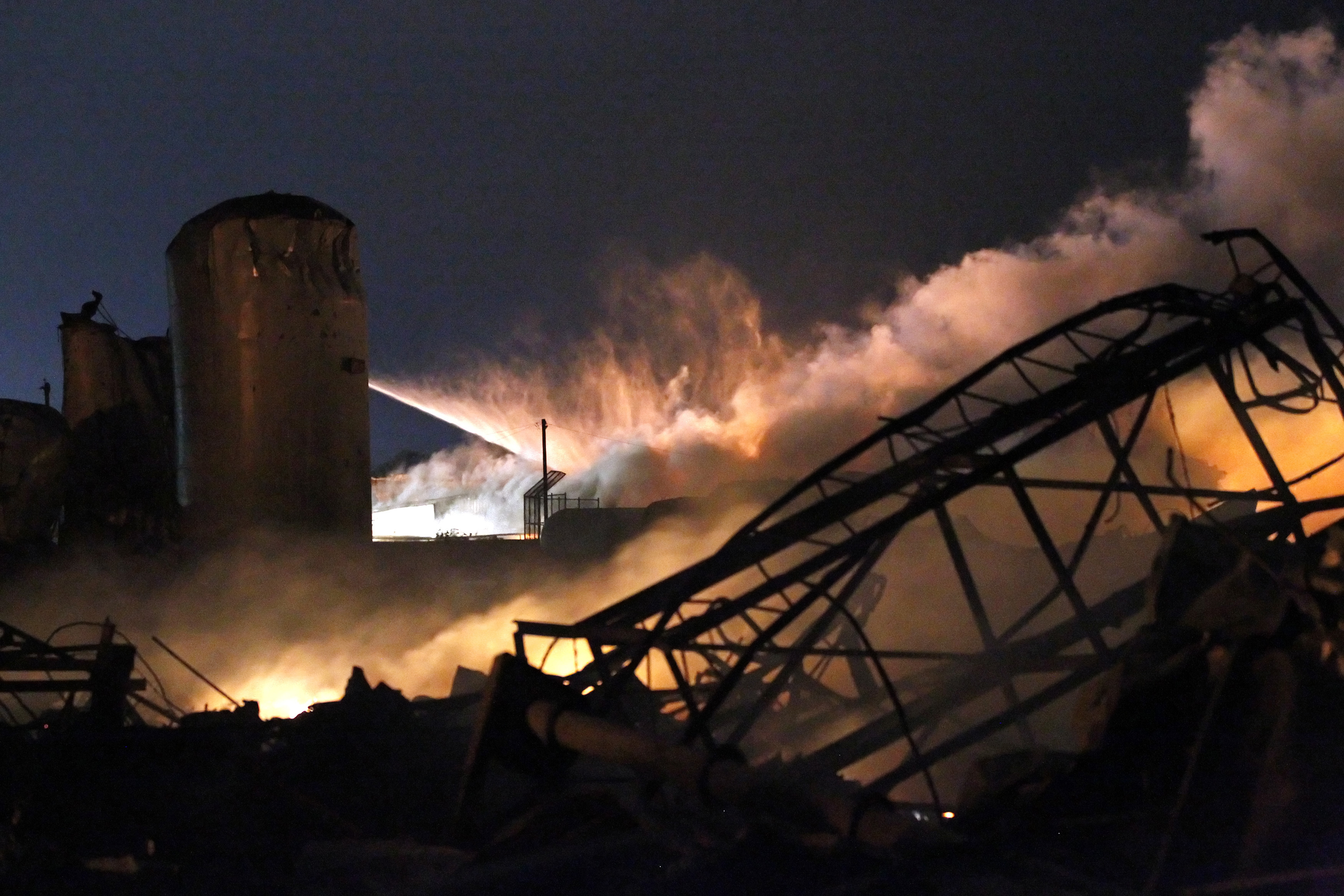 Smoke rises as water is sprayed after an explosion at a fertilizer plant in the town of West, Texas.