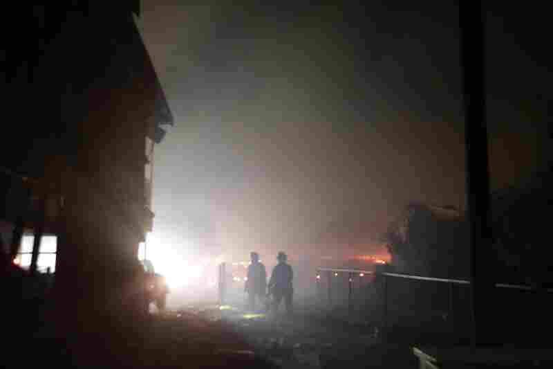 Firefighters search an area destroyed by the explosion.