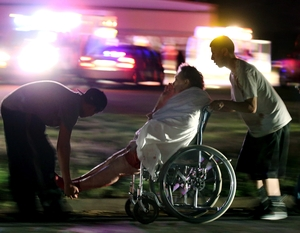 An injured person is assisted by two men as a nursing home is evacuated after the explosion.