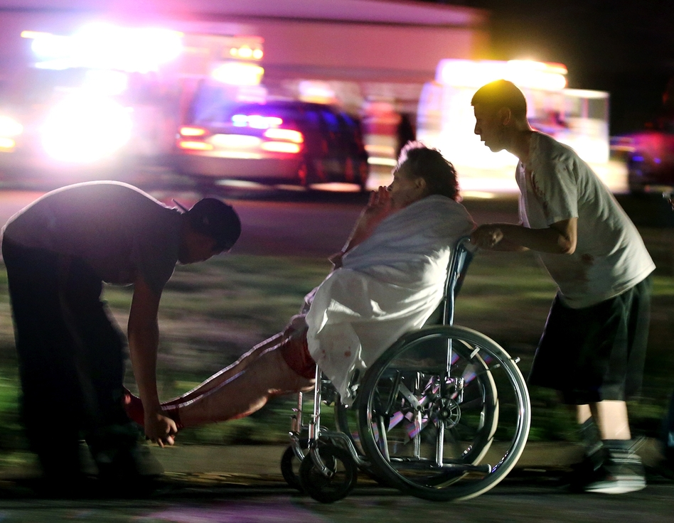 An injured person is assisted by two men as a nursing home is evacuated after the explosion. (AP)
