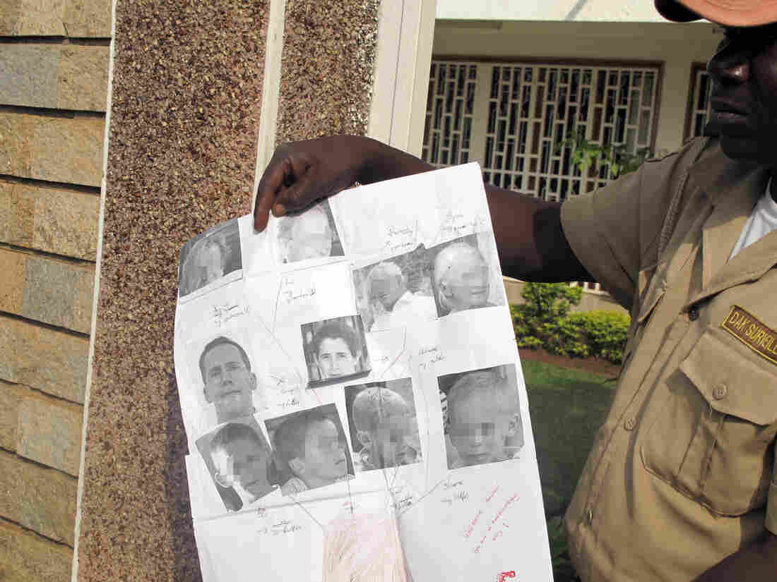 A security guard in Cameroon shows photos of Tanguy Moulin-Fournier and his wife, Albane, and their four children, in February.