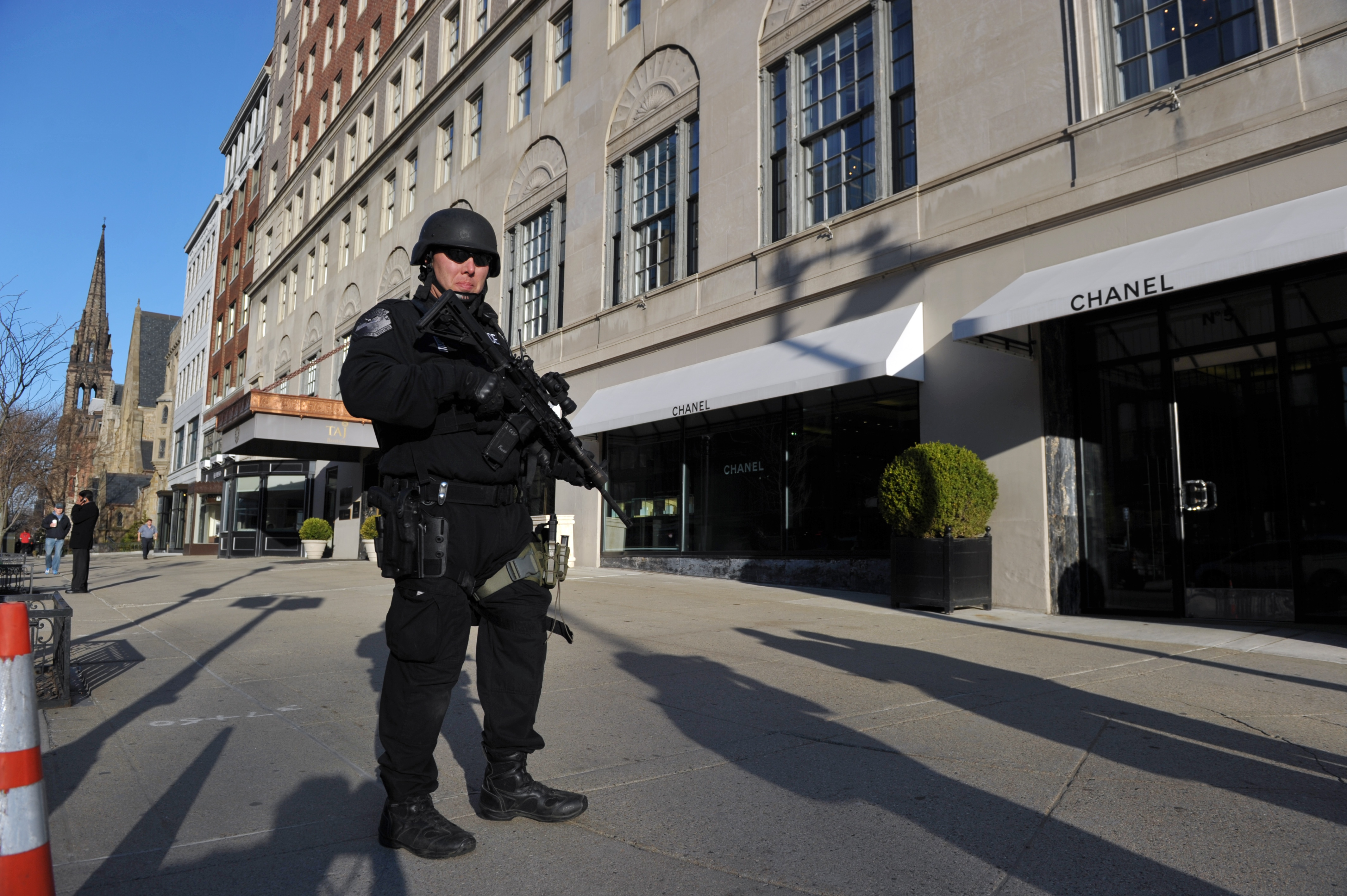 A heavily armed Boston police officer stands guard in front of the Taj Hotel on Tuesday.