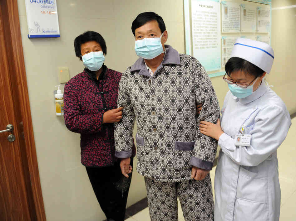 An H7N9 bird flu patient is escorted after his recovery and approval
