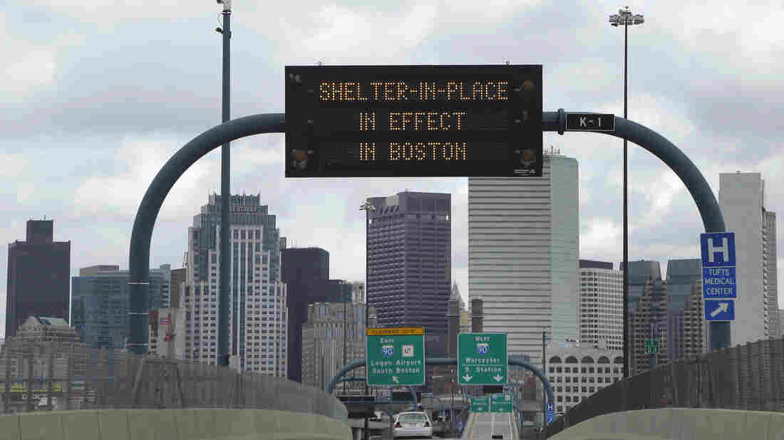 "A sign calling for citizens of Boston to ""Shelter in Place"" hung across I-93 Friday in Boston."
