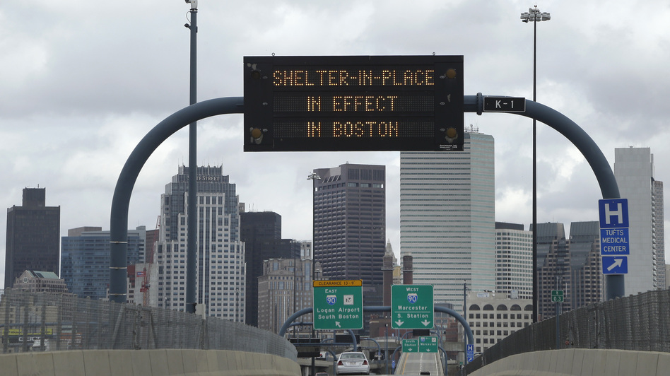 "A sign calling for citizens of Boston to ""Shelter in Place"" hung across I-93 Friday in Boston. (AP)"