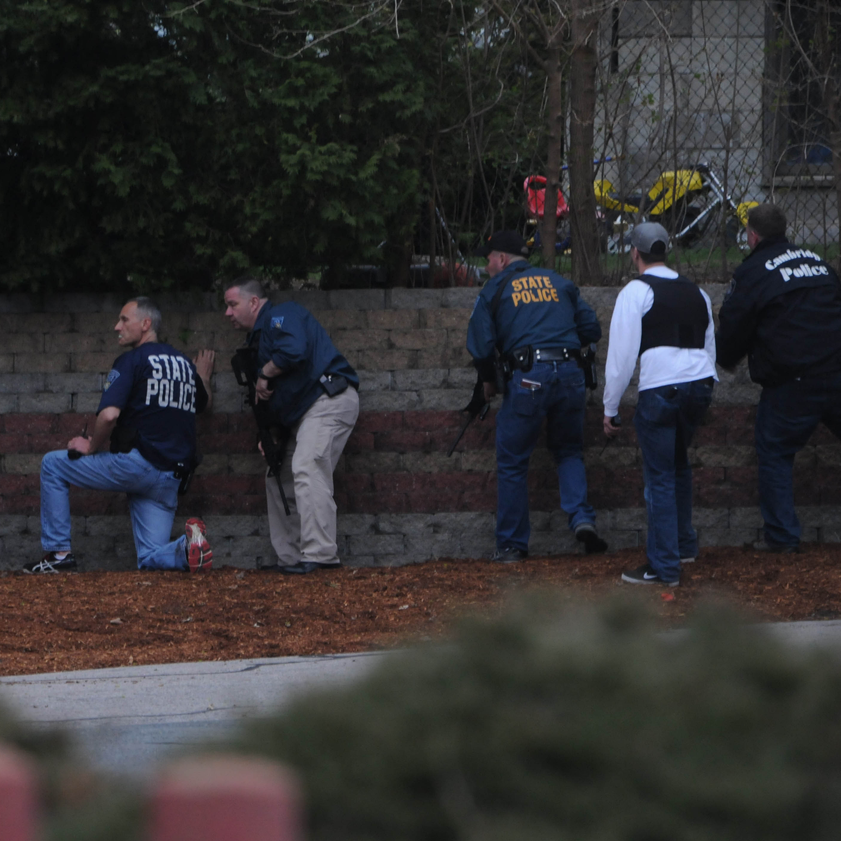 Law enforcement approach an area where a suspect is reportedly hiding in Watertown, Mass