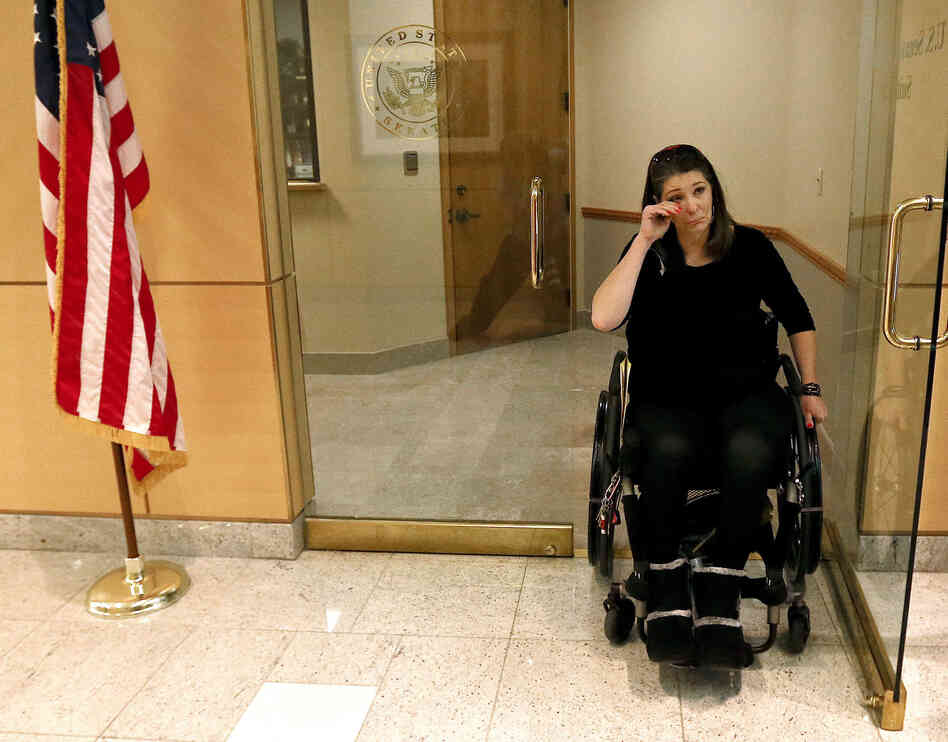 Jennifer Longdon, who survived gun violence but was left a paraplegic, wiped away tears at an April 19, 2013 protest at Arizona Republican Sen. Jeff Flake's Phoenix office.