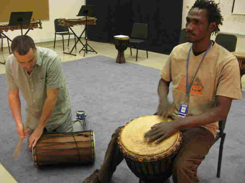Teacher Paul Chandler (left) and musician Siaka Doumbia play djembe drums during music class.