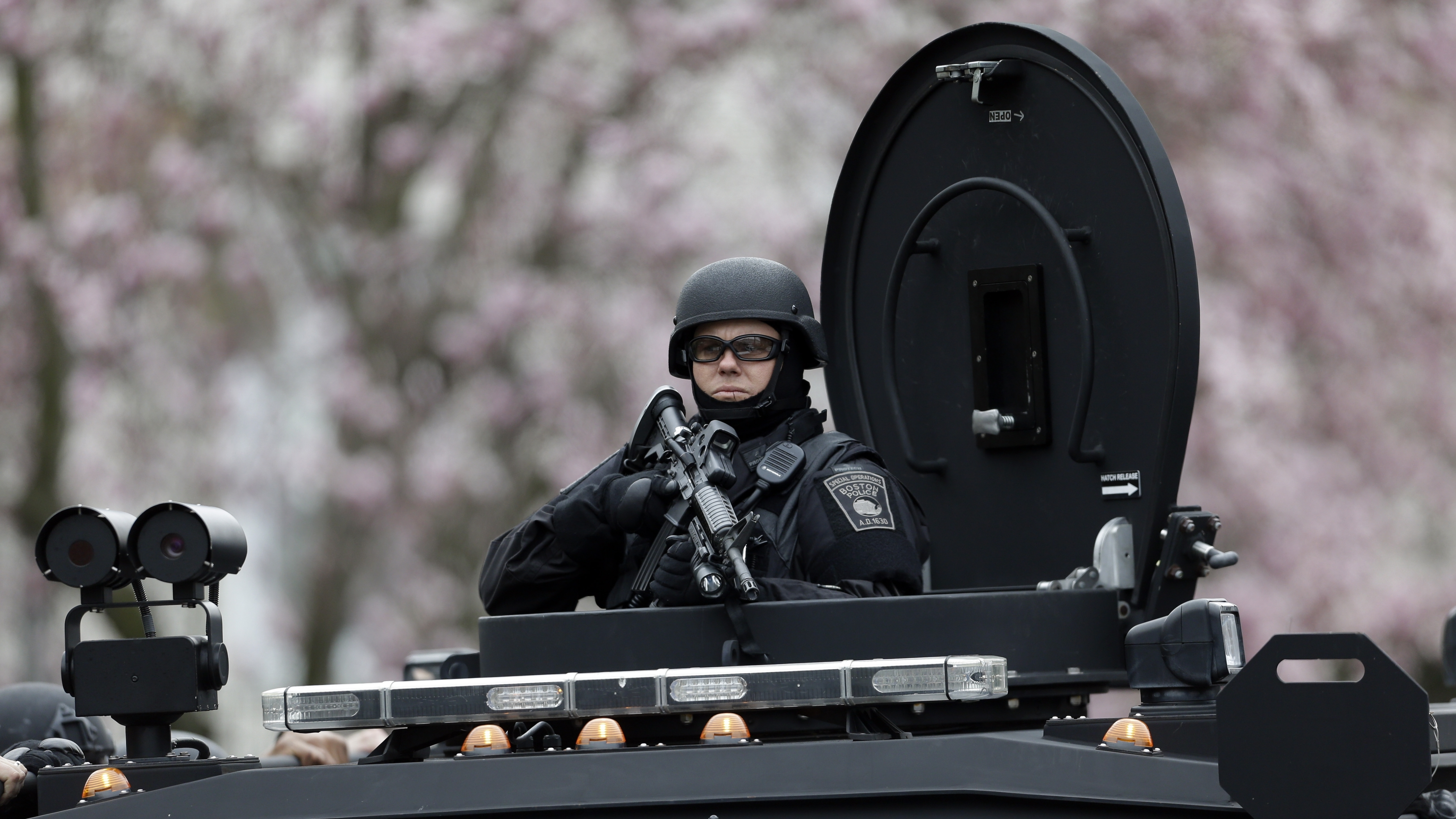 A police officer in tactical gear conducts a search for a suspect in the Boston Marathon bombings in Watertown, Mass.