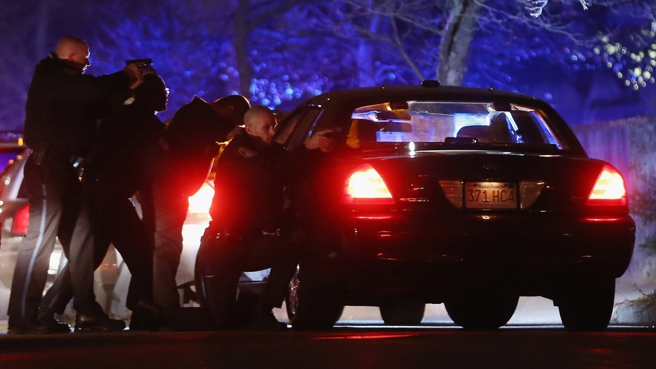 Police with guns drawn search for one of the Boston Marathon suspects early Friday in Watertown, Mass. (Mario Tama/Getty Images)