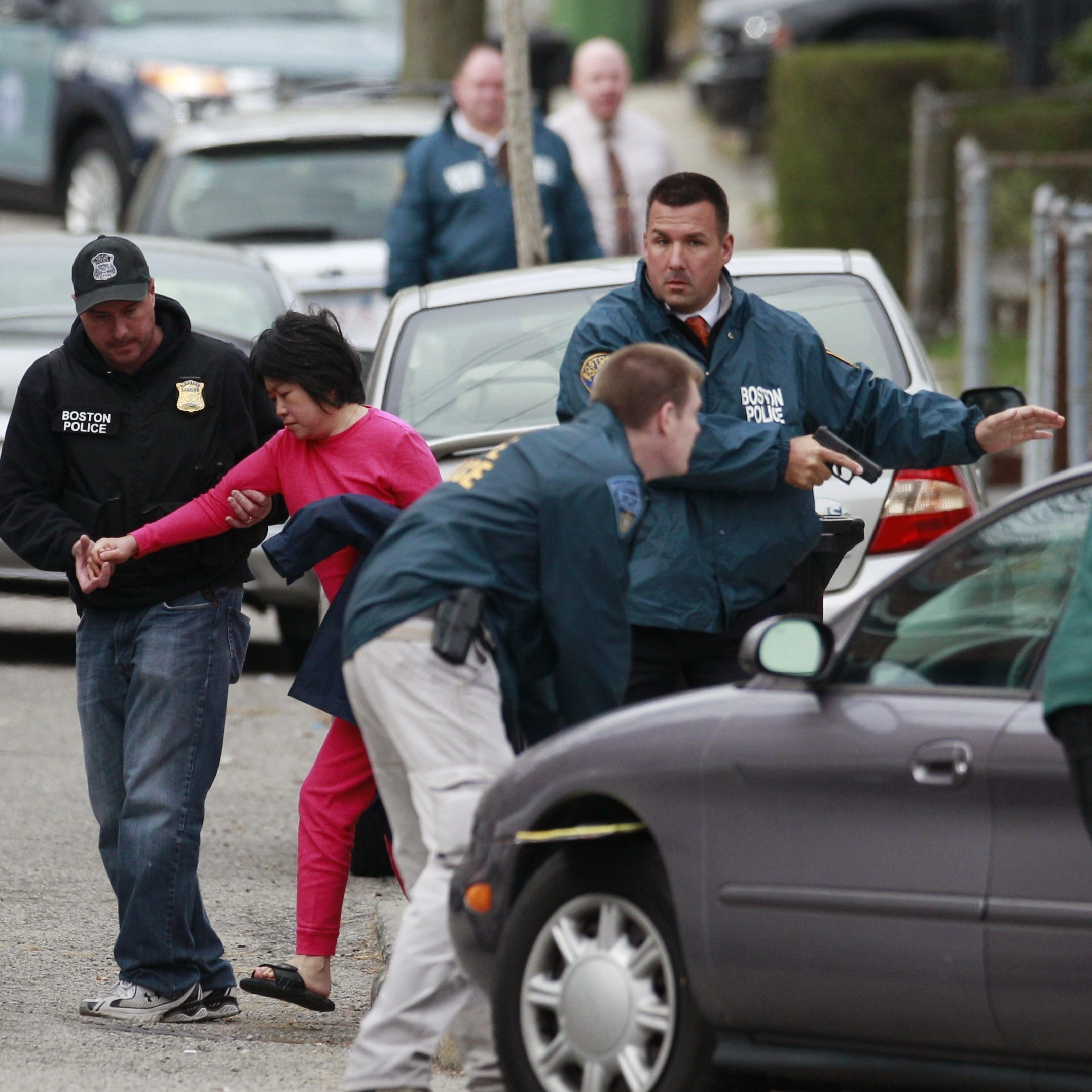 A neighbor is escorted to safety as police surround a home in Watertown.