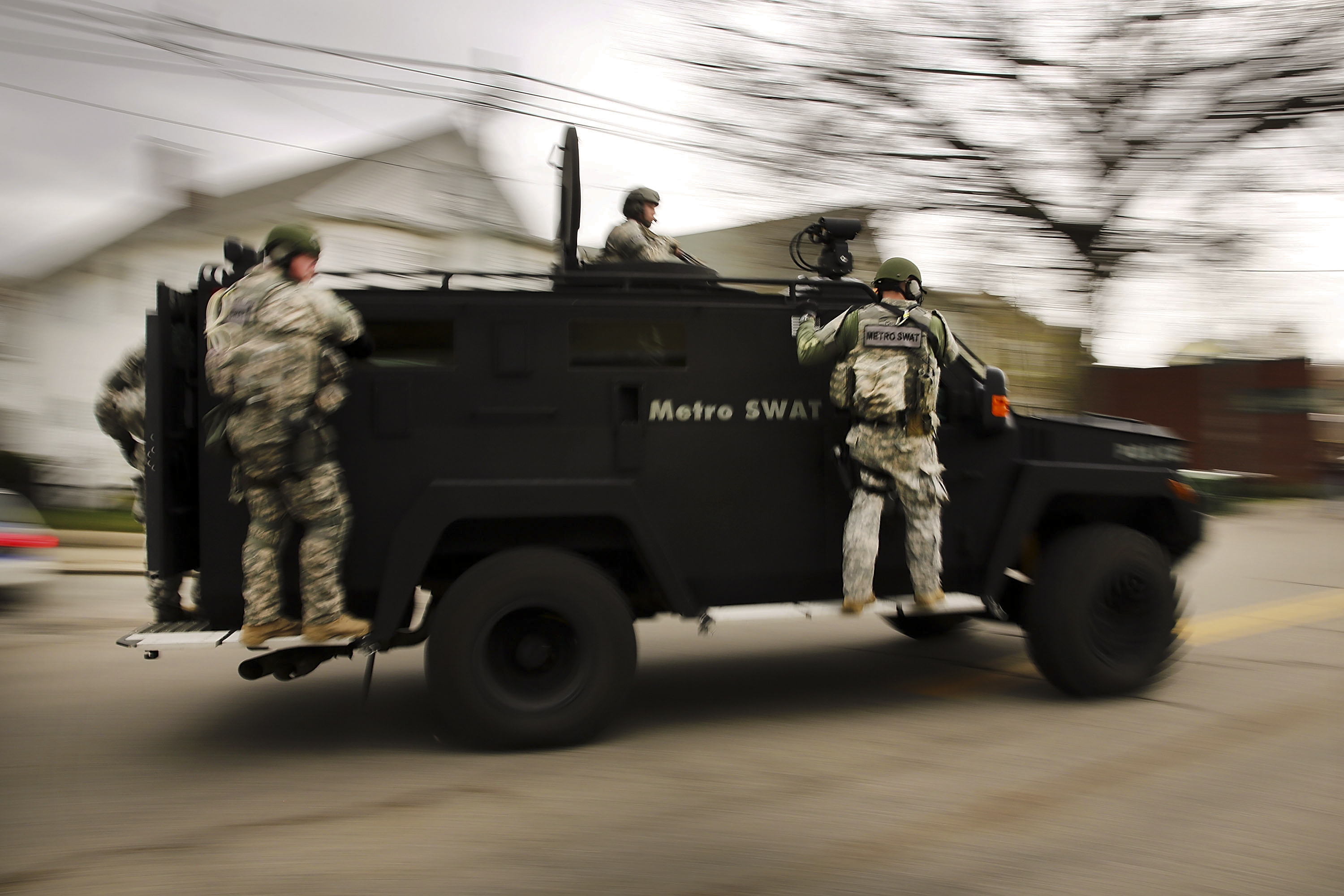 Members of a police S.W.A.T. team search a neighborhood in Watertown.