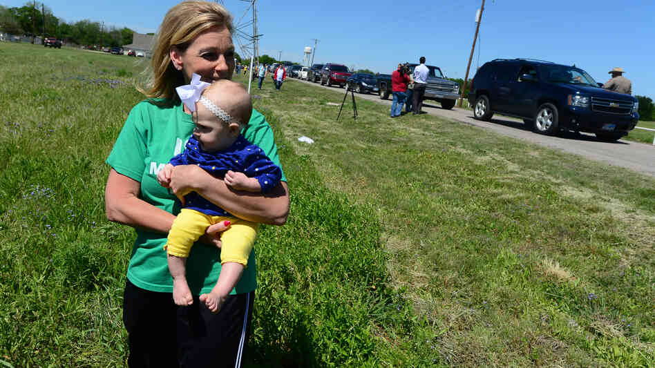 Debby Keel holds her grandchild, Kennedy, as Texas Highway Patrol officers record the entry of residents who are allowed to return to their homes near the site of the April 17 fertilizer plant blast in West, Texas.