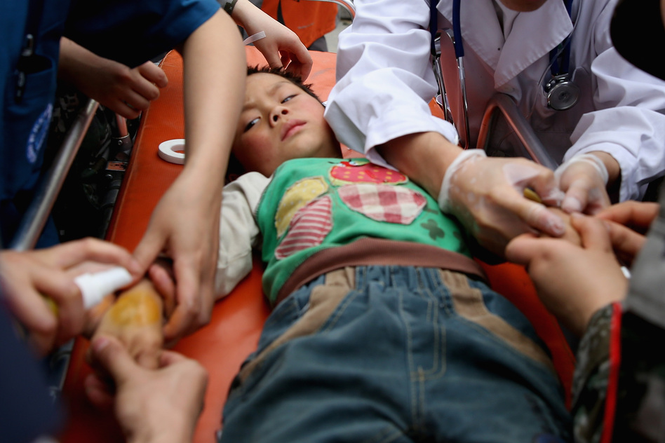 Medical officers treat a patient at the hospital on Sunday in Lushan of Ya'an. (Getty Images)