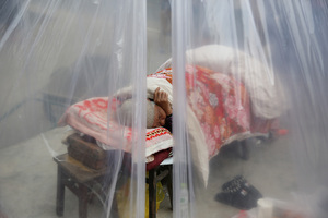 An earthquake survivor sleeps in a tent on Sunday in Lushan.