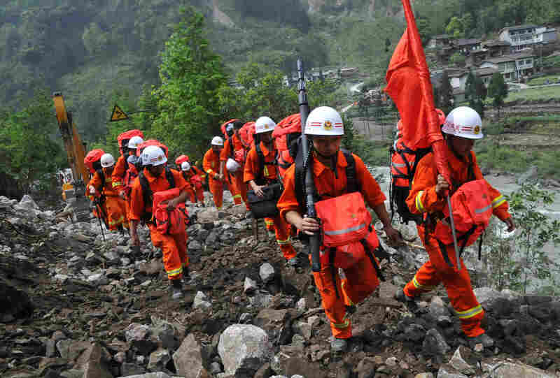 Chinese rescuers walk through wreckage to reach isolat