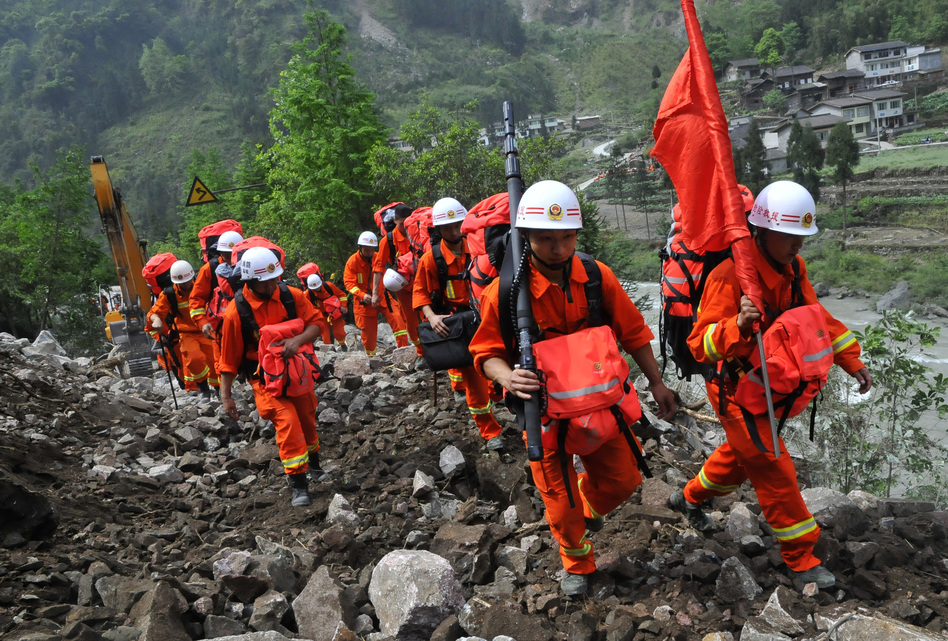 Chinese rescuers walk through wreckage to reach isolated Baoxing country after the earthquake in Ya'an, southwest China's Sichuan province on Sunday.