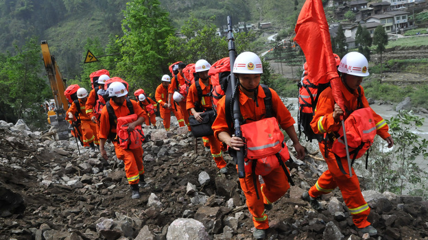 Chinese rescuers walk through wreckage to reach isolated Baoxing country after the earthquake in Ya'an, southwest China's Sichuan province on Sunday. (AFP/Getty Images)