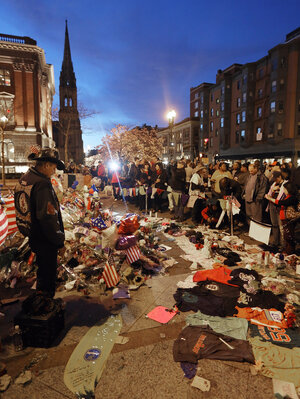 People gather at a makeshift memorial for victims of the Boston Marathon bombings at the edge of the still-closed section of Boylston Street. The surviving suspect in the case
