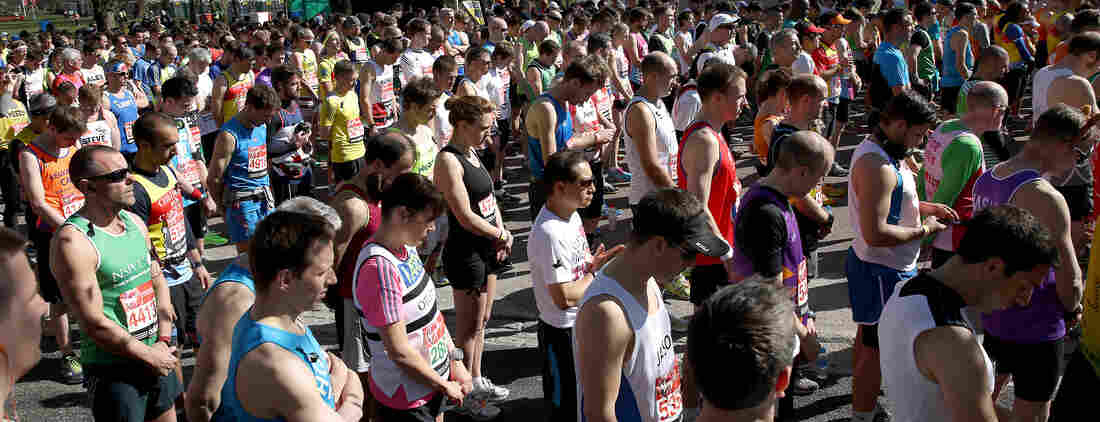 London Marathon runners stand in a silent, pre-race tribute Sunday to the victims of the Boston Marathon bombings. The police presence was increased for the London event.